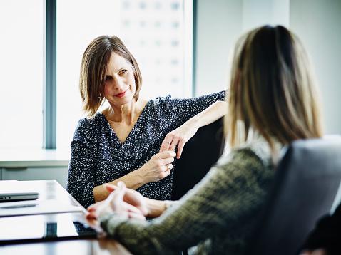 Mulheres conversando em ambiente corporativo